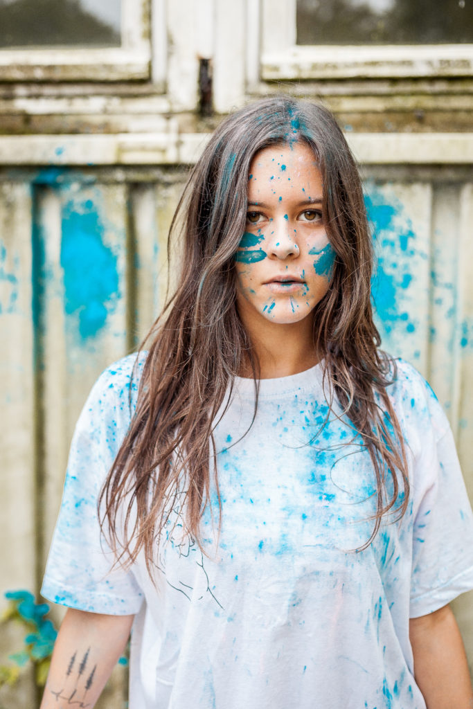 beautiful girl with brown eyes, white shirt and blue colour in her body in front of painted wall