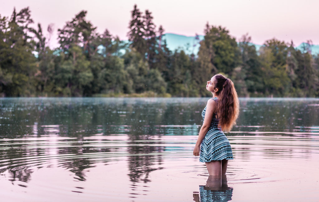 beautiful reflective water with a young lady wearing a short dress and having long hair standing in it