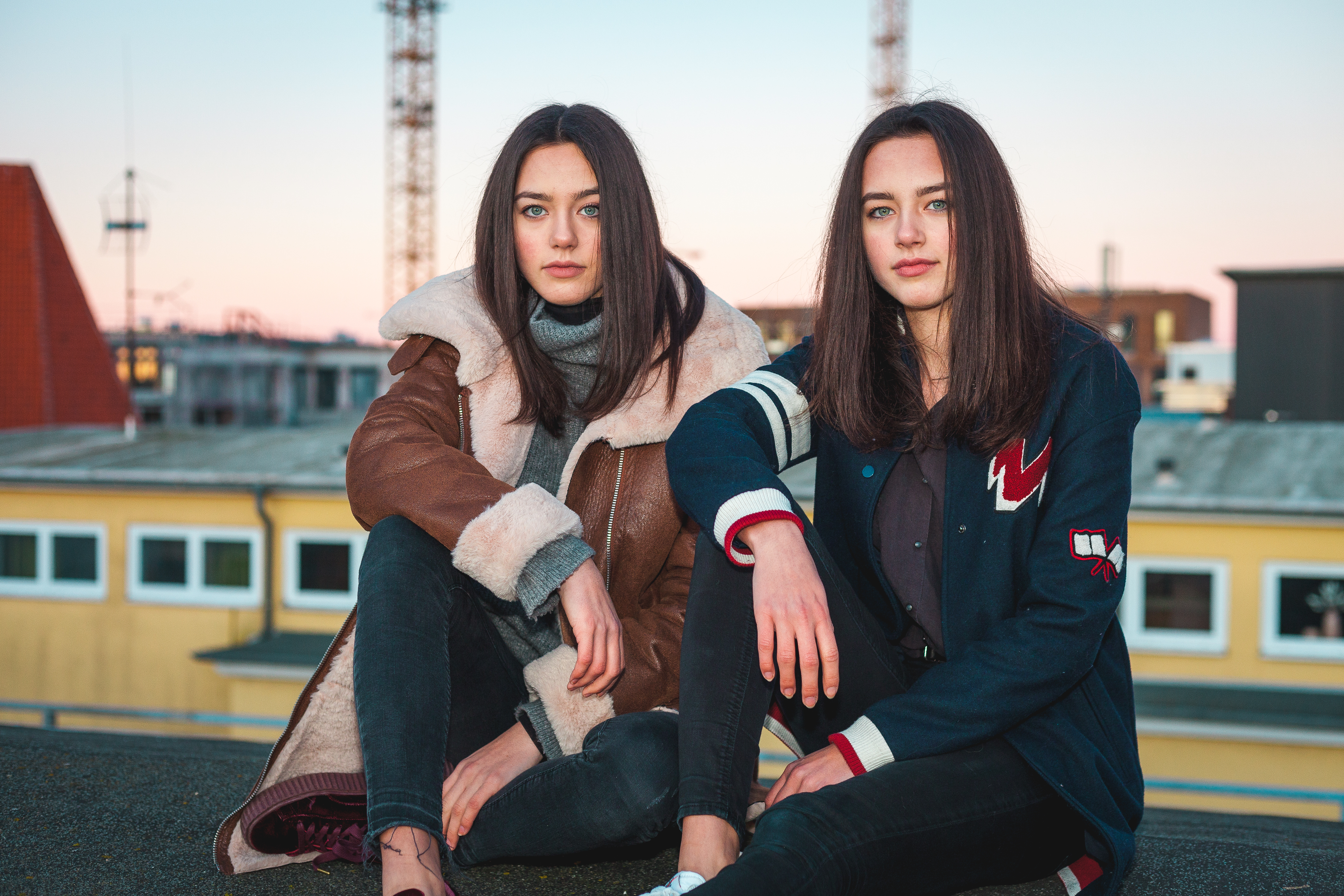 Two beautiful twins in lovely sunlight at the evening standing on a roof with the city behind them