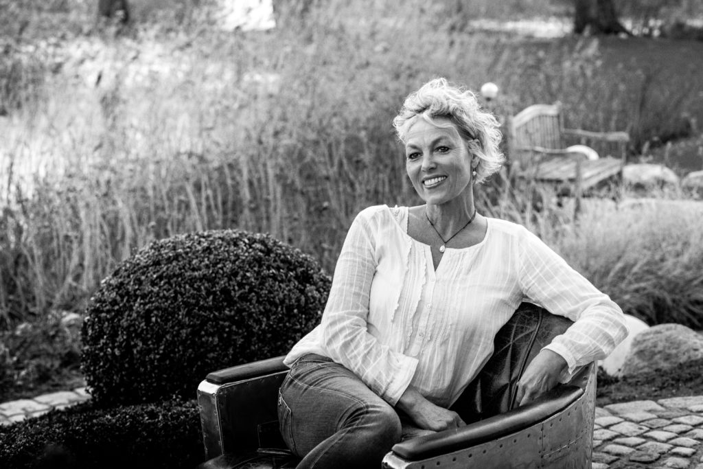 smiling women wearing a white blouse sitting in a designer chair in front of reed in a garden