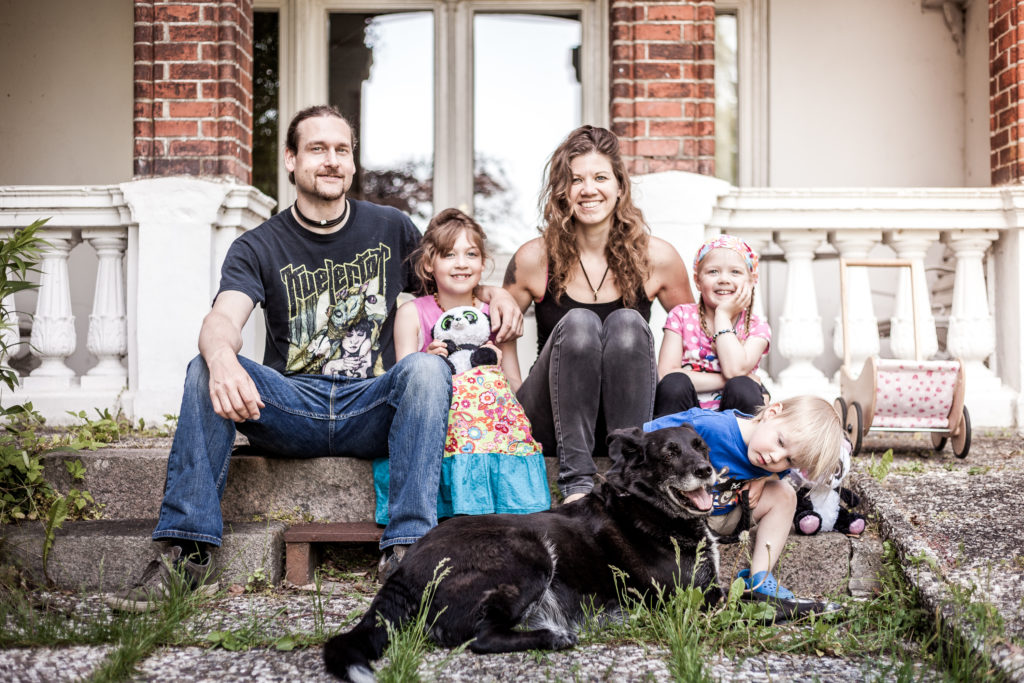 smiling family with black dog, two little girls, a little boy and parents