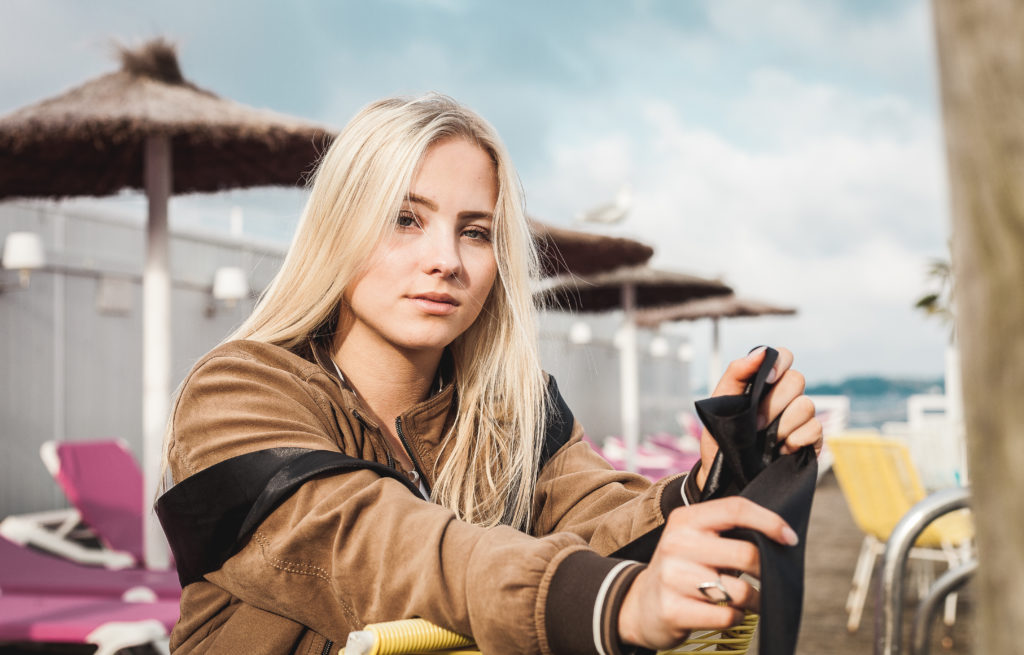 beautiful blond model wearing leather jacket sitting on a chair close to the sea