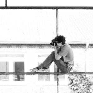 photographer sitting on a scaffold taking a picture, black and white