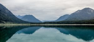 Landscape in bavaria of a beautiful blue barrier lake in the Alps, the water reflects the sky and mountains