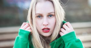 young lady with blue eyes, red lips, blond hair and green pullover looking into the camera